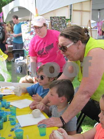 Teagan Grandors and Sam Salvatore were ready to create clay pots at the kids tent with assistance from Sue Posie who was with Salvatore.