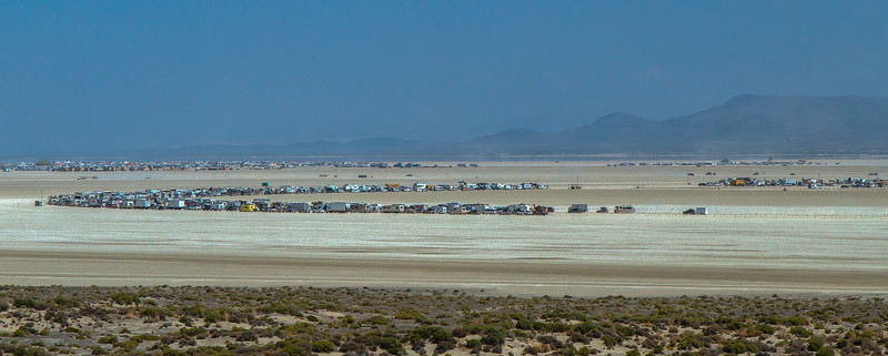 17011 Long lines starting to form at the entrance of Black Rock City which officially opens at midnight. These cars, trucks and RVs will remain parked here until then. It's a comfortable 100 degrees.