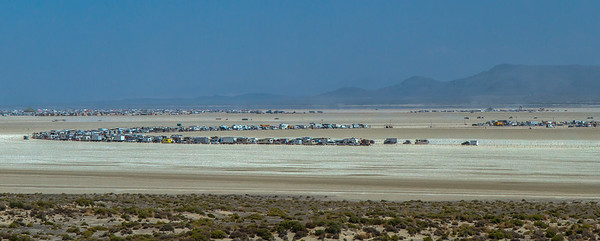 17024 Long lines starting to form at the entrance of Black Rock City which officially opens at midnight. These cars, trucks and RVs will remain parked here until then. It's a comfortable 100 degrees.