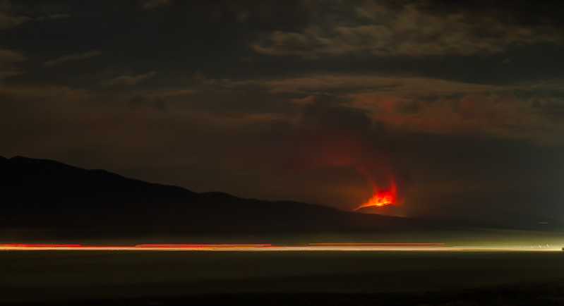 17002 The Tohakum 2 Fire burns south of Empire as vehicles drive on the playa to Black rock City