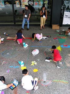 "A CHALK 4PEACE volunteer and organizer inspire the artists,  CHALK 4PEACE"" Sidewalk Chalk Contest,  Dr. MLK Jr. Memorial Library, DC, 7-15-05"