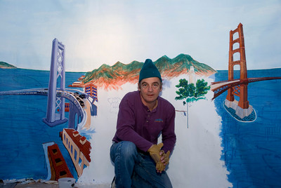 "Installation Day, The mural-Playland Not at the Beach, El Cerrito, CA Artist with ""Bygone San Francisco"" mural. It is the backdrop to a diorama from Playland's collection of historic porcelain buildings in an elborate depiction of  San Francisco at the time of the Golden Gate International Exposition of 1939. Measuring 24 feet by 7 feet, with a complex curved perspective, the mural depicts  the East Bay and Marin County shortly after both bridges opened. The mural is still in progress; it was commissioned by Playland Not at the Beach."