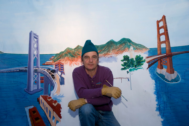 """Installation Day, The mural-Playland Not at the Beach, El Cerrito, CA Artist with """"Bygone San Francisco"""" mural. It is the backdrop to a diorama from Playland's collection of historic porcelain buildings in an elborate depiction of  San Francisco at the time of the Golden Gate International Exposition of 1939. Measuring 24 feet by 7 feet, with a complex curved perspective, the mural depicts  the East Bay and Marin County shortly after both bridges opened. The mural is still in progress; it was commissioned by Playland Not at the Beach."""
