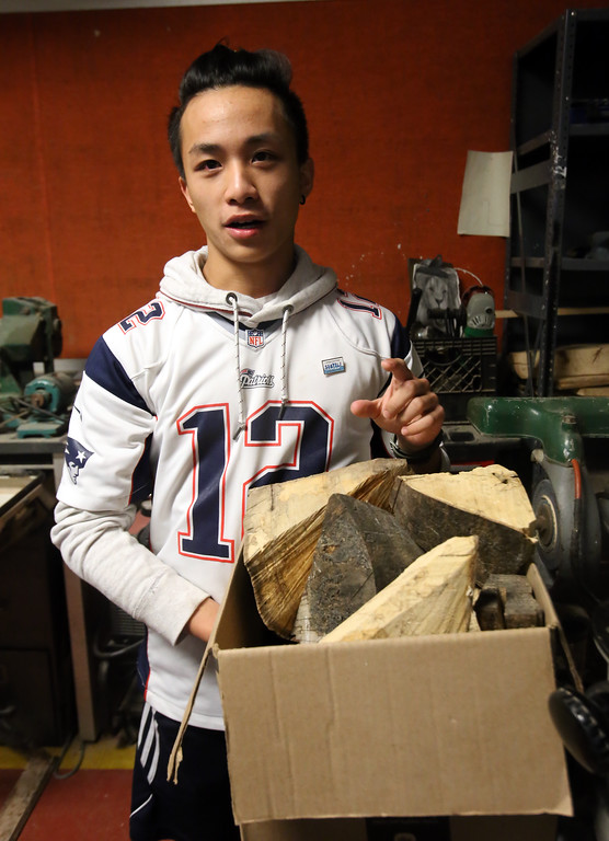 . Chelmsford High senior Felix Huang, 18, with leftover wood from his section of the purple beech that had to be cut down on Chelmsford Town Common in 2013. (SUN/Julia Malakie)