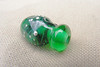 This lampwork mini-vessel is about 2.5 cm long by about 1.5 cm wide. Created with transparent green glass, fine silver wire, and swirls of aqua filigrana glass, the green glass of this mini-vessel shimmers under the fine silver wire dots.