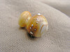 This lampwork mini-vessel is about 1.9 cm long by about 1.5 cm wide. Created with opaque dark ivory glass, silver reduction frit and fine silver wire, this little vessel displays a range of color from ivory to caramel and butterscotch.