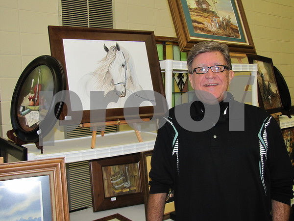 Lee Husske beside some of his paintings done in oil or watercolor.