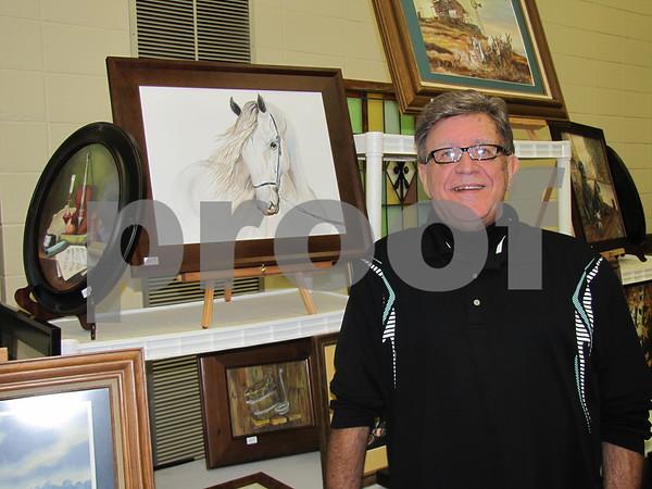 Lee Husske beside some of his paintings done in oil or watercolor.