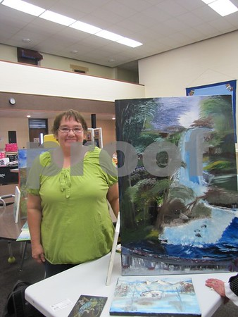 Stacy Spencer, artist, stands beside one of her paintings at the Community Artists Sale.