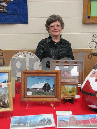 "Millie Nordeen with art created by local artists who display at ""By the Grace of God"" church in Barnum."