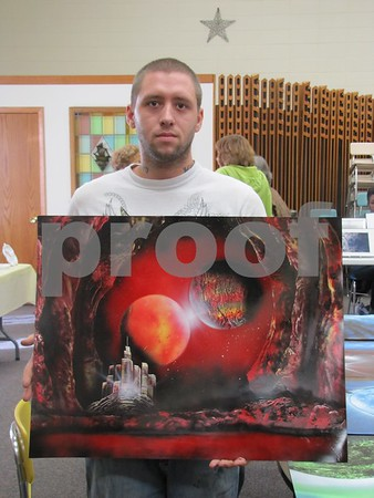Michael Dreke with one of his unique paintings using a spray can technique.