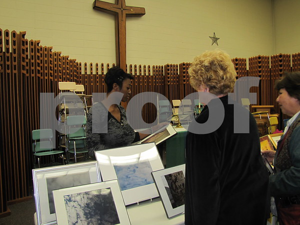 Qunetta McCaleb, photographer, visits with some ladies about her photos.