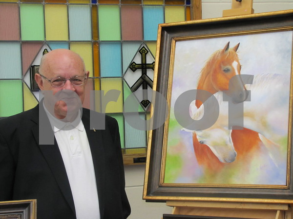 Hal HInds stands beside a painting his wife, Mary Jo Hinds, painted.  Hinds was managing the booth of her paintings for her at the Community Artists Sale.