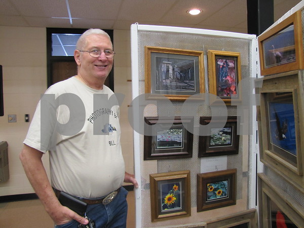 Bill Keenan next to a display of his photography.
