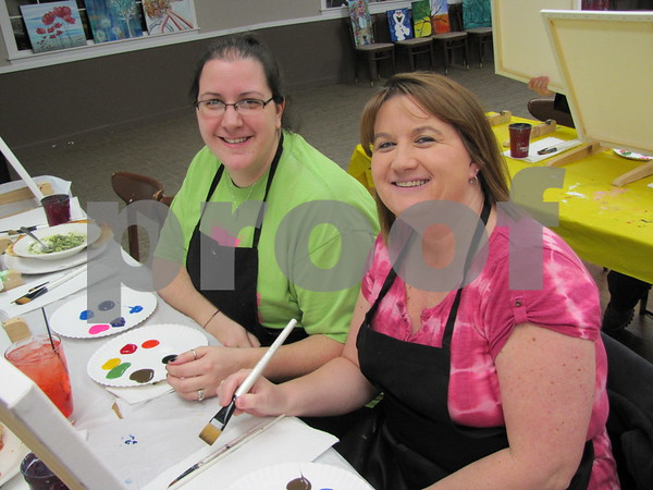 Gina Grobe and Melissa Hansen are ready for an evening of fun and creativity at the 'Creative Spirits' painting class held at The Cellar.