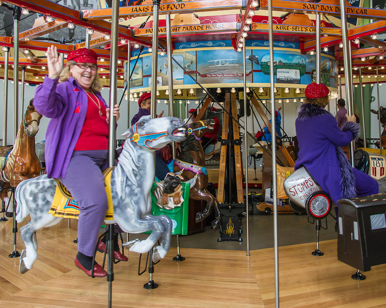 The red hat ladies try out the carousel