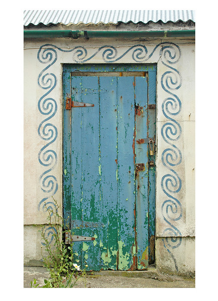 Blue door with wave pattern and tin roof, England.