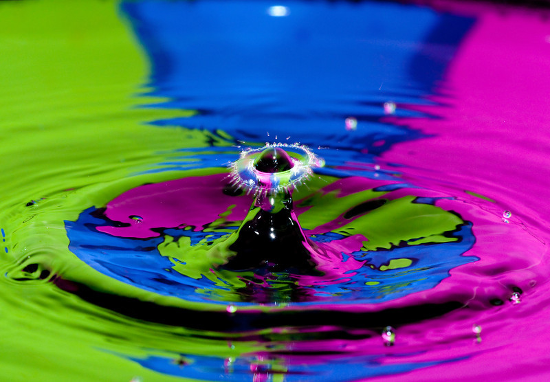 a droplet impact in front of a brightly colored background