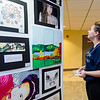 Jordan Jones takes a closer look at the art on display during the Evening with the Arts at Oakmont on Friday evening. SENTINEL & ENTERPRISE / Ashley Green