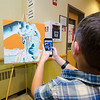 Ben Tshudy, 9, takes a photo of some interactive art during the Evening with the Arts at Oakmont on Friday evening. SENTINEL & ENTERPRISE / Ashley Green