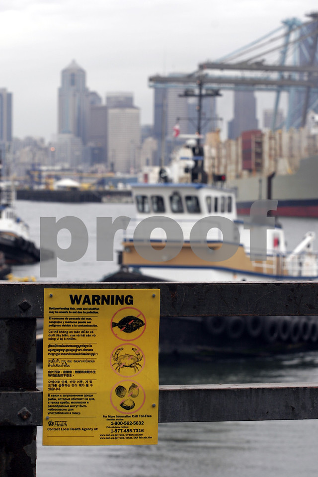 A sign in multiple languages advises readers of the dangers of consuming fish and shell fish in the Duwamish River waterway in Seattle, WA.