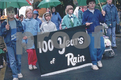 School children celebrate Washington State's centennial by honoring 100 years of rain. WA.