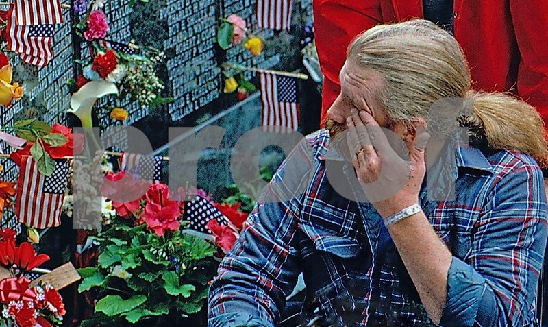 A disabled war veteran weeps at the Vietnam Memorial in Olympia, WA.