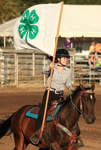 A young girl carrying the 4H flag at a local rodeo. WA.