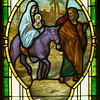 "I recently heard somebody at church refer to this as the ""purple donkey"" window.  I took another look at the window and said to myself, ""Oh yeah..that's purple!""  Maybe Povey Bros. had some excess inventory of purple glass that they wanted to get rid of.  (Although it is more likely that the color is painted on, not in the glass.)"