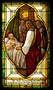 This window is apparently an illustration of the story of Lazarus being raised from the dead.  The quote at the bottom of the window is from that passage in the Bible.  However, the picture itself looks more like the story of Jesus healing the young daughter of a prominent man.