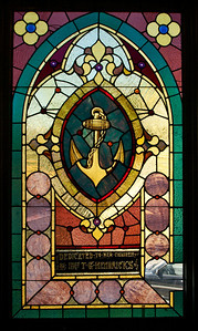 This window and those following are from the earlier group of windows.  They depict fairly conventional religious symbols.  We will never know who made the windows.  It is possible that Povey Bros. made them.  If not, they were shipped to Eugene from some unknown studio in the east, because nobody else was making stained glass in this part of the country at the time.  (Note the dedication mentioning Mrs. T. G. Hendricks.  Thomas G. Hendricks was a prominent name in Eugene history; he was a banker.  Hendricks Park, of rhododendron fame, is names for him.  He is buried in Eugene Masonic Cemetery.)  (Also note the damage in the lower right corner of this window.  It looks like a piece was broken out and replaced with clear glass.)