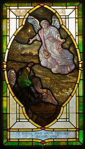 """The PoveyBrothers windows in the sanctuary consist of 2 main groups.  The first is a set of 12 """"medallion style"""" windows ranging along the walls of the lower part of the sanctuary and in the narthex.  They depict scenes from the life of Christ.  In this one the angel is proclaiming the news of the birth of Jesus to the shepherds.  If you look at it close up you will see places where the paint is wearing off."""