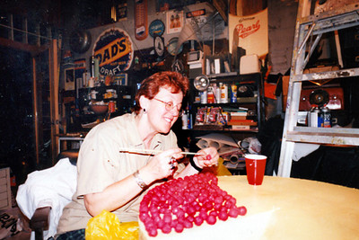 Betty Lark Ross at work in the studio preparing the rubber coating on each of the cherries placed on the cheesecake for our cow, Mooving Eli, for Cows On Parade.