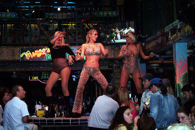 Slice of life on Ocean Drive. Dancers mount the bar while party goes around around them.