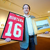 """Fitchburg Art Museum Director Nick Capasso holds a signed Joe Montana jersey and a painting by Fitchburg Superintendent Andre Ravenelle. The two items are among many others being sold in an online auction currently running at the website  <a href=""""http://www.biddingforgood.com"""">http://www.biddingforgood.com</a>, Thursday. The auction ends Thursday, February 6th at noon.<br /> SENTINEL & ENTERPRISE / BRETT CRAWFORD"""