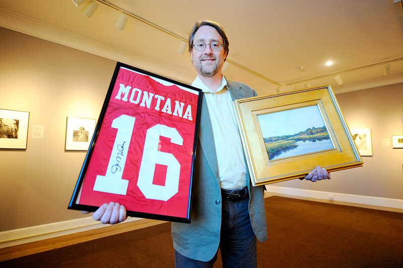 "Fitchburg Art Museum Director Nick Capasso holds a signed Joe Montana jersey and a painting by Fitchburg Superintendent Andre Ravenelle. The two items are among many others being sold in an online auction currently running at the website  <a href=""http://www.biddingforgood.com"">http://www.biddingforgood.com</a>, Thursday. The auction ends Thursday, February 6th at noon.<br /> SENTINEL & ENTERPRISE / BRETT CRAWFORD"