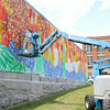 Caleb Neelon, 38, works on a mural on the wall of the Arc of Opportunity building in downtown Fitchburg on Monday afternoon. SENTINEL & ENTERPRISE/JOHN LOVE