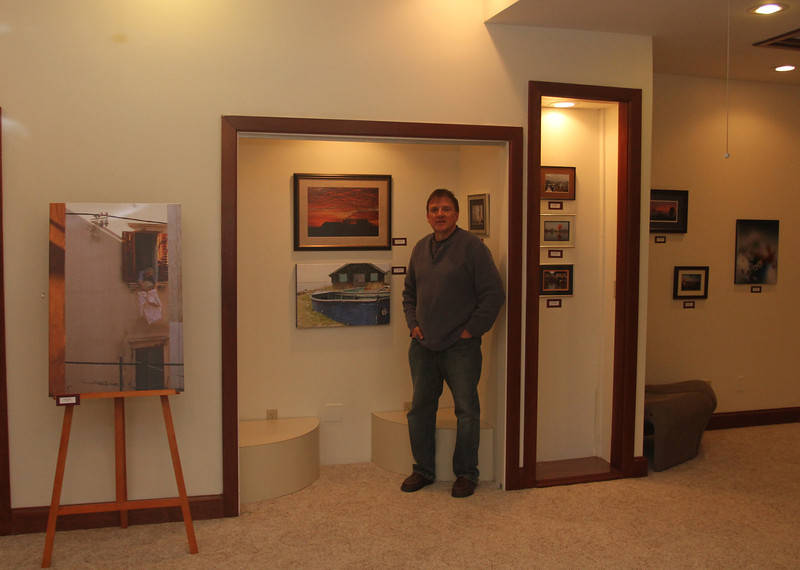 Kent with some of his displayed photographs at the GMOA.