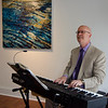 John Hansen entertains the crowd on the piano during the opening of Gallery Sitka at 454 Main Street in Fitchburg on Friday morning. SENTINEL & ENTERPRISE / Ashley Green