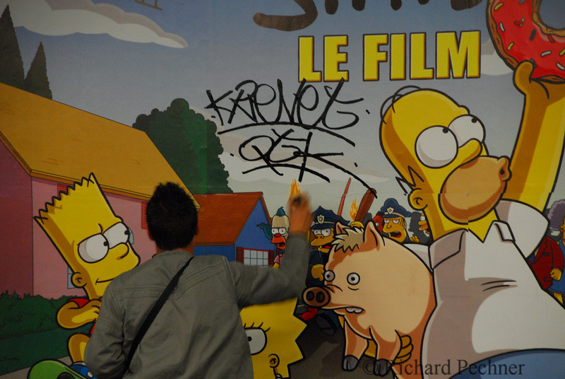 Krevet finishing off his tag on Simpson movie poster in the Metro.
