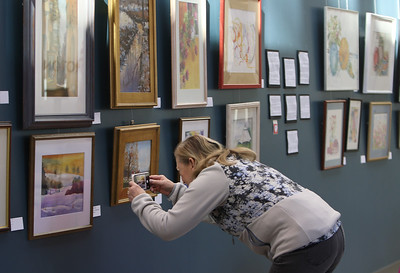 Babs Dasilva of Groton, takes photos of some of the paintings at The Groton Center (Council on Aging), for inspiration. She does watercolor painting herself. The show of Nashoba Valley artists who paint at the Center on Mondays, includes paintings by Barbara Badstubner,Valerie Baier, Nancy Dey, Shirley Man, Peg McWade, Connie Sartini and Ellen Todd, and is up until April. The new senior center/community center opened in November.(SUN/Julia Malakie)