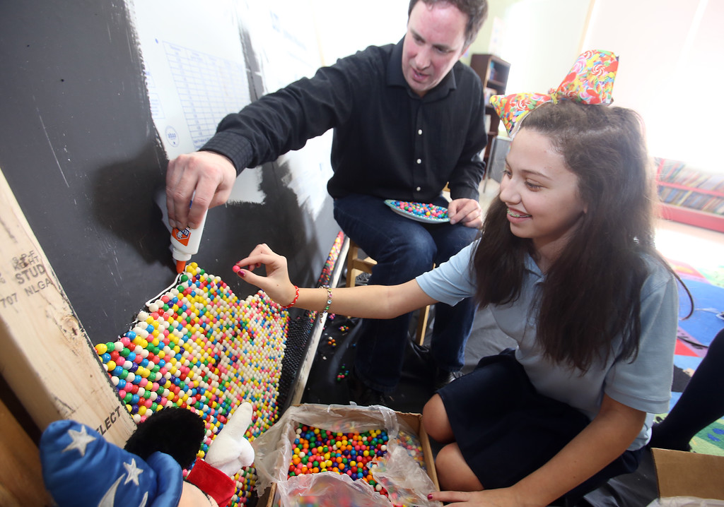 . Artist Rob Surette of Andover works with Hellenic American Academy students on a pointillism work made with gumballs. Surette adds glue for sixth grader Ava Regan, 12, of Ashby, to place a gumball. Surette mostly told the students what color to place, but occasionally said \'pick any color.\' (SUN Julia Malakie)