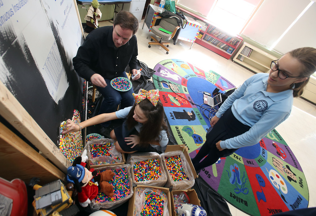 . Artist Rob Surette of Andover works with Hellenic American Academy students on a pointillism work made with gumballs. Sixth graders Ava Regan, 12, of Ashby, placing a gumball, and Briana Hardy, 11, of Chelmsford waiting her turn. (SUN Julia Malakie)
