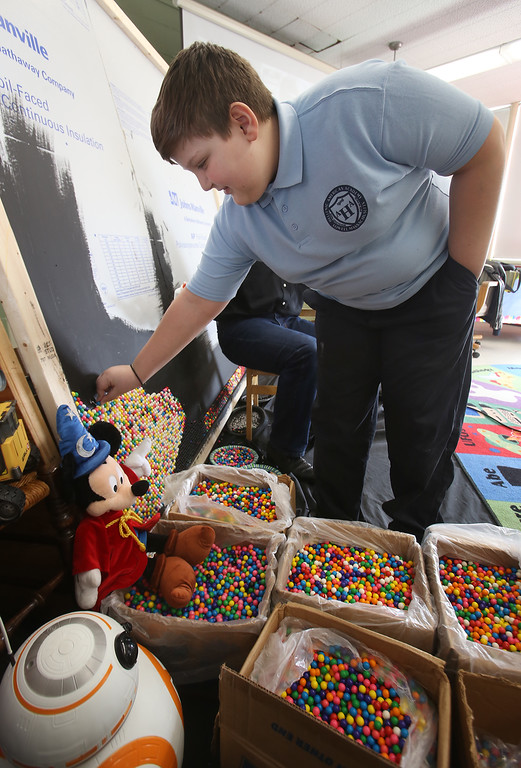 . Artist Rob Surette of Andover works with Hellenic American Academy students on a pointillism work made with gumballs. Themistocles Pelekoudas, 11, of Tyngsboro, takes a turn placing a gumball. (SUN Julia Malakie)
