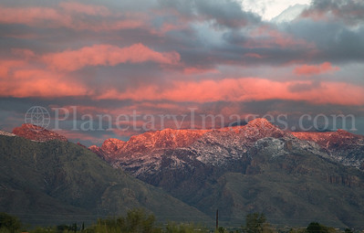 Pink sunset light shines on the show-capped Catalina Mountains in Tucson.
