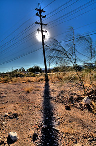 The January sun captured behind a power line pole.