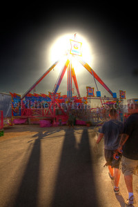 The sun appears to be an atomic explosion behind a Pima County Fair amusement ride.