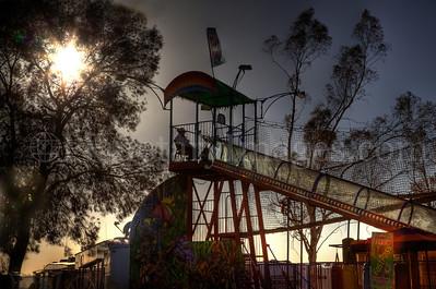 The sun blazes through a tree as a man mans his post at a Pima County Fair amusement ride.