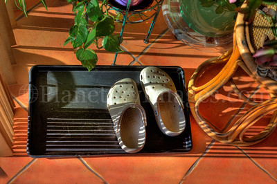 Clogs near my kitchen sliding door receive the late day sunlight and shadows.