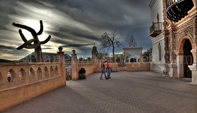 The entrance to the famous San Xavier near sunset with dramatic clouds in Tucson, Arizona